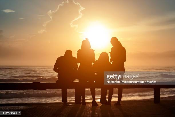 silhouette people at beach during sunset - vier personen stockfoto's en -beelden