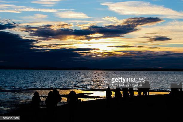 silhouette people at beach during sunset - artur petsey foto e immagini stock