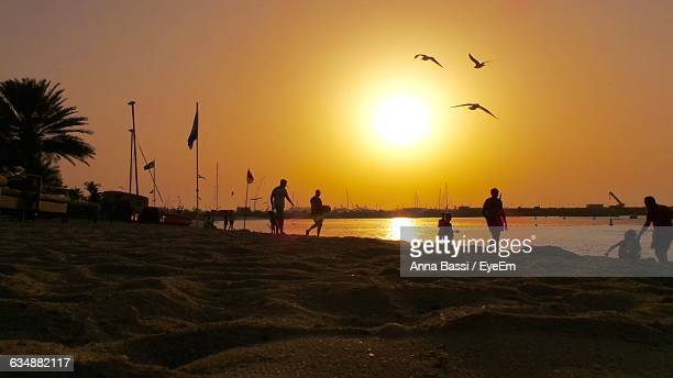 silhouette people at beach during sunset - weekend activities stock pictures, royalty-free photos & images
