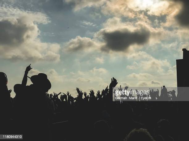 silhouette people at music concert against sky - popular music concert stock pictures, royalty-free photos & images