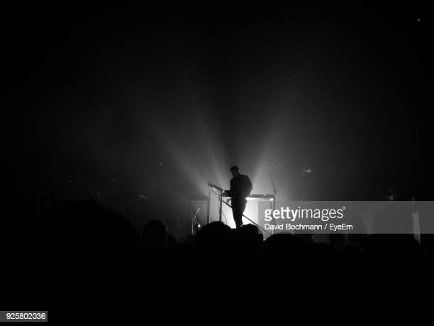 silhouette people at music concert - filter band stock photos and pictures