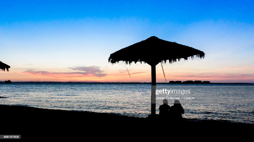 Silhouette People Below Thatched Roof Parasol At Beach Against Sky During Sunset : Stock Photo