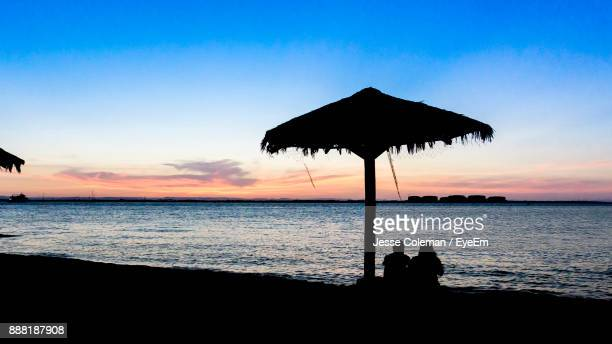 silhouette people below thatched roof parasol at beach against sky during sunset - jesse coleman stock pictures, royalty-free photos & images