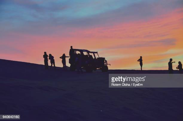 Silhouette People By Buggy At Desert During Sunset