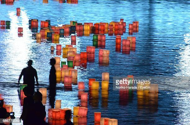 silhouette people by colorful illuminated lanterns on lake at night - hiroshima fotografías e imágenes de stock