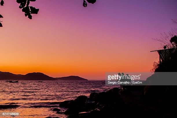 Silhouette People By Sea Against Clear Purple Sky During Sunset