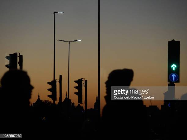 silhouette people by stoplights against sky at night - costangelo pacilio foto e immagini stock