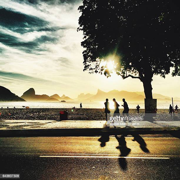 silhouette people enjoying at beach against sky during sunset - niteroi stock pictures, royalty-free photos & images