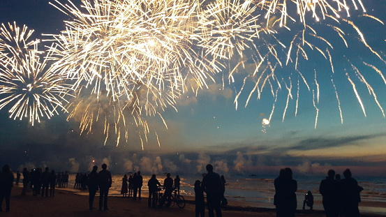Silhouette People Enjoying Illuminated Firework Exploding Against Sky At Beach During Sunset - gettyimageskorea