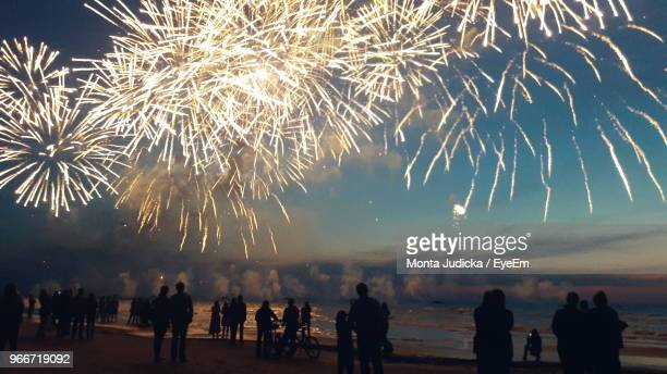 silhouette people enjoying illuminated firework exploding against sky at beach during sunset - firework display stock pictures, royalty-free photos & images