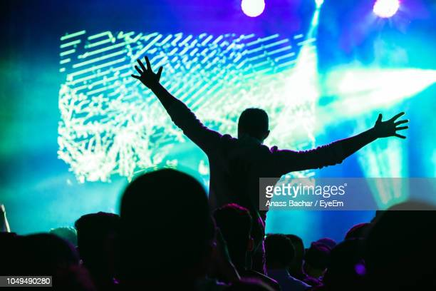 Silhouette People Enjoying Music Concert At Night