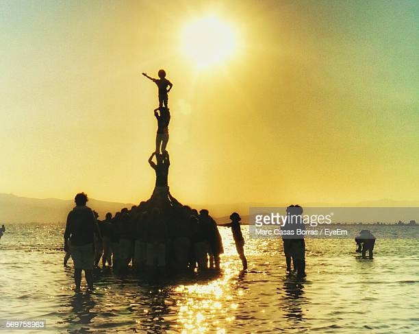 silhouette people forming pyramid at beach against sky during sunset - pyramid stock pictures, royalty-free photos & images