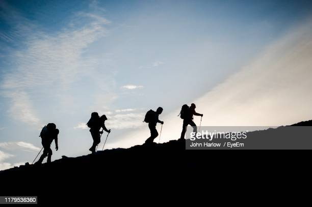 silhouette people hiking on mountain against sky - backpacker stock pictures, royalty-free photos & images