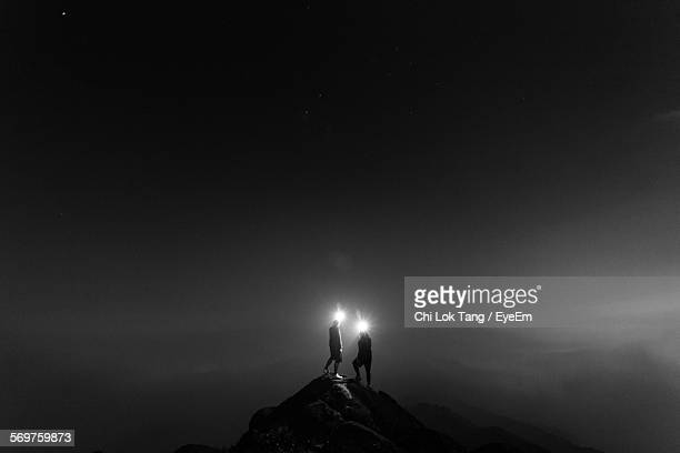 silhouette people holding light on top of mountain against sky at night - guidance stock pictures, royalty-free photos & images