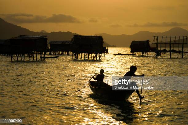 silhouette people in boat against sea during sunset - shaifulzamri stock pictures, royalty-free photos & images