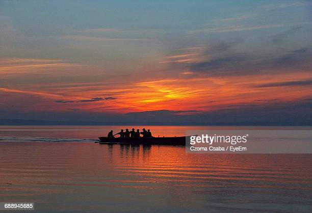 silhouette people in boat at sea against sky during sunset - medium group of people stock pictures, royalty-free photos & images