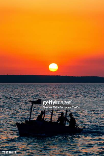 Silhouette People In Boat Sailing On Sea Against Orange Sky