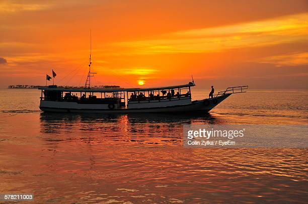 Silhouette People In Ferry Boat Against Orange Sunset Sky