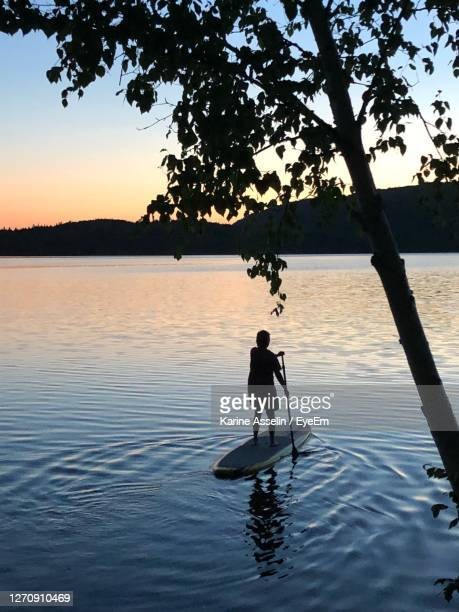 silhouette people in lake against sky during sunset - karine asselin stock pictures, royalty-free photos & images