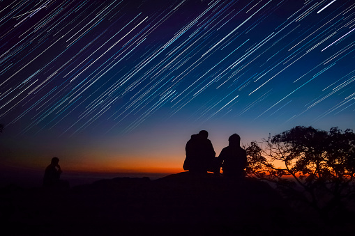 Silhouette People Looking At Star Trails Against Sky During Sunset - gettyimageskorea