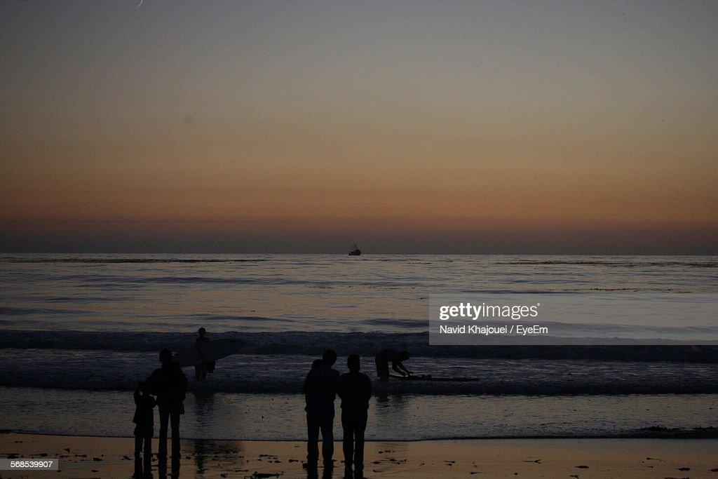 Silhouette People On Beach Against Sky At Sunset : Stock Photo