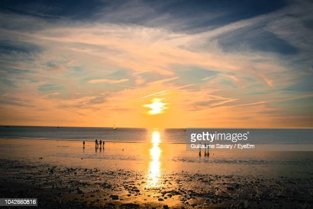 silhouette people on beach against sky during sunset - ouistreham stock pictures, royalty-free photos & images