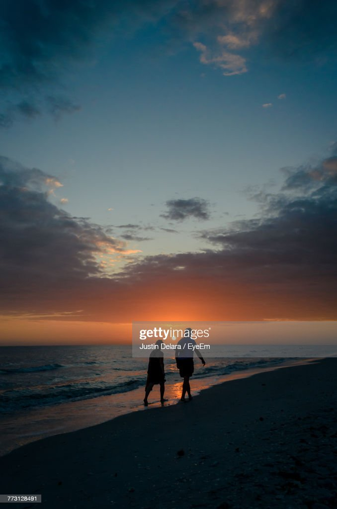 Silhouette People On Beach Against Sky During Sunset : Photo