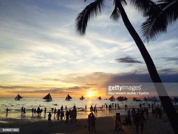 silhouette people on beach against sky during sunset - davao city stock photos and pictures