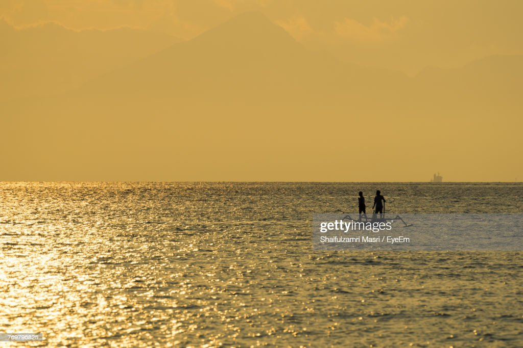 Silhouette People On Boat At Sea Against Orange Sky : Stock Photo