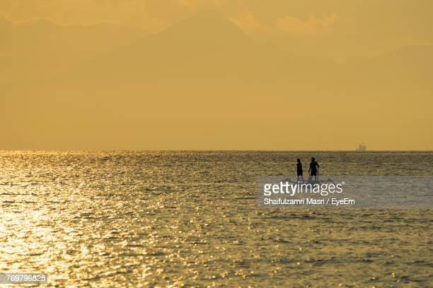 silhouette people on boat at sea against orange sky - shaifulzamri eyeem stock pictures, royalty-free photos & images