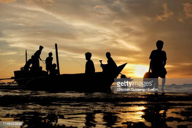 silhouette people on boat in sea against sky during sunset - medium group of people stock pictures, royalty-free photos & images