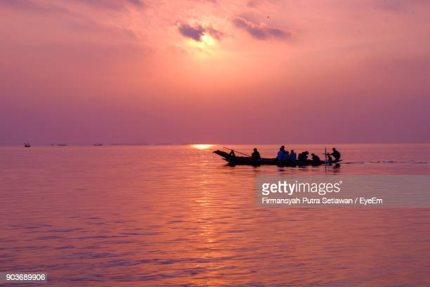 silhouette people on boat in sea against sky during sunset - east java province stock photos and pictures