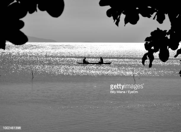 Silhouette People On Boat In Sea Against Sky