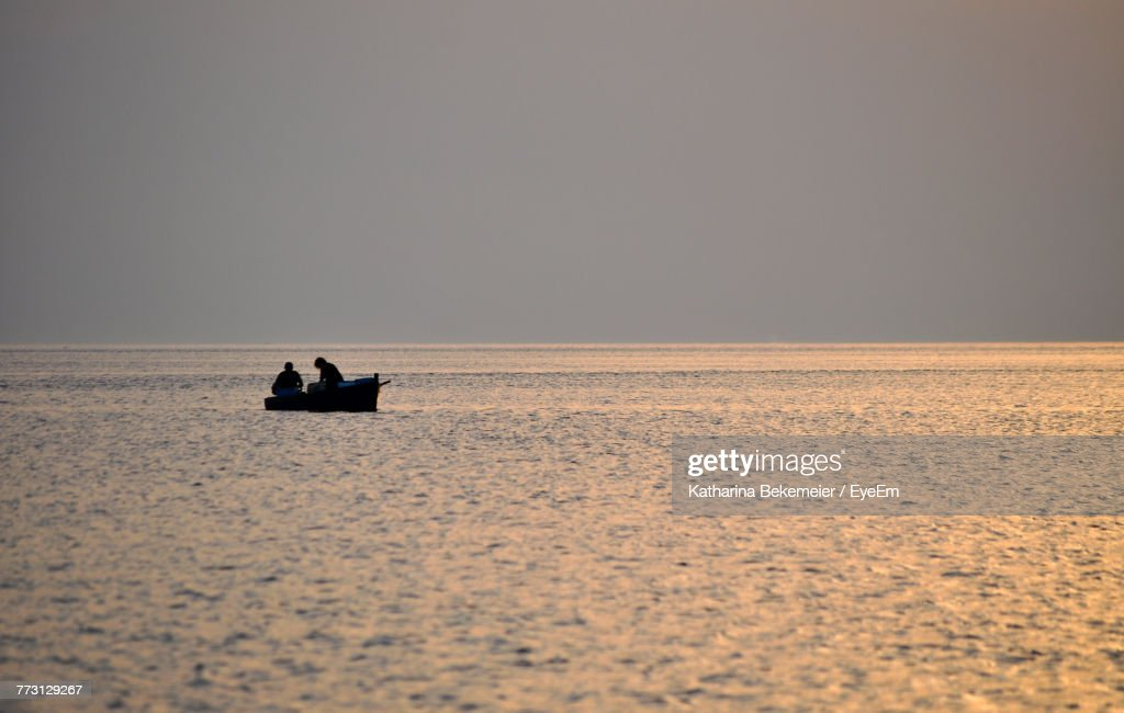 Silhouette People On Boat In Sea Clear Sky During Sunset : Photo