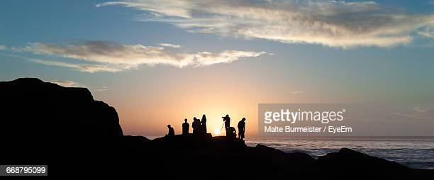 Silhouette People On Cliff Against Sky During Sunset