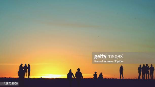 silhouette people on field against sky during sunset - coral springs stock pictures, royalty-free photos & images