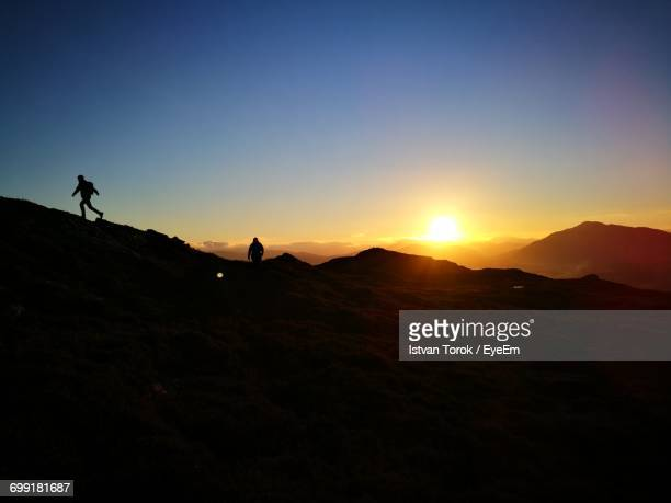 Silhouette People On Mountain Against Clear Sky During Sunset