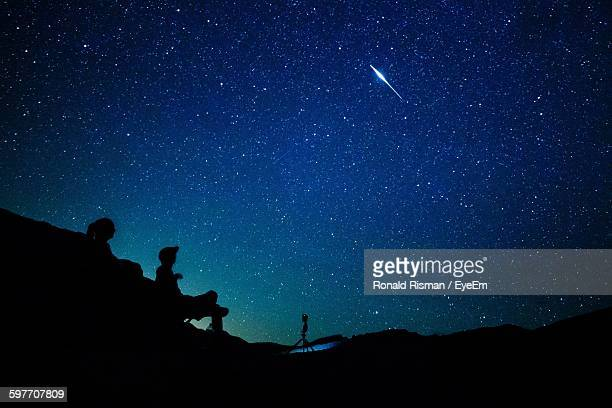 silhouette people on mountain against stars in sky - costellazione foto e immagini stock