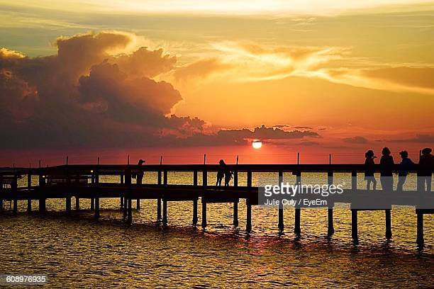 silhouette people on pier over sea against sky during sunset - julie culy stock pictures, royalty-free photos & images