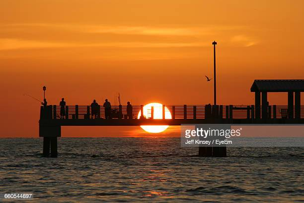 silhouette people on pier over sea against sky during sunset - st. petersburg florida stock photos and pictures