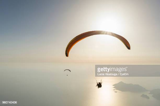 silhouette people paragliding over sea against sky - glider stock photos and pictures
