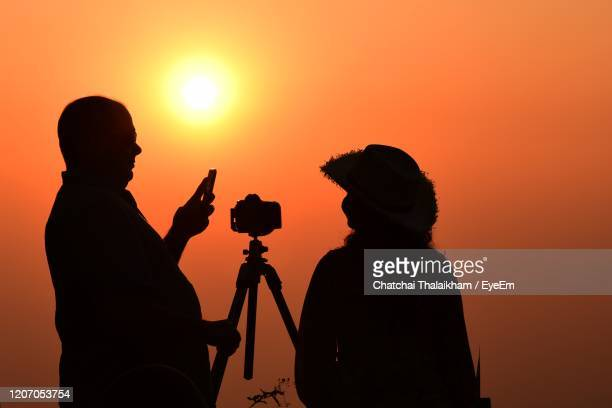 silhouette people photographing orange sky during sunset - chatchai thalaikham stock pictures, royalty-free photos & images