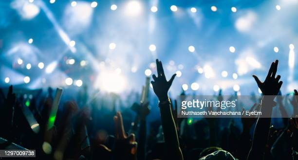 silhouette people raising hands at popular music concert - music festival stock pictures, royalty-free photos & images