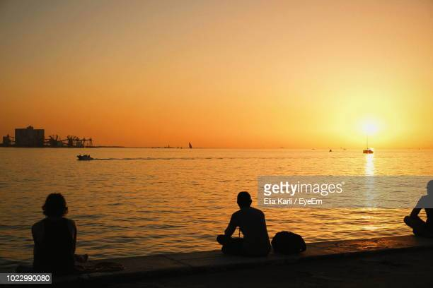silhouette people sitting at beach against clear sky during sunset - elia karli stock-fotos und bilder