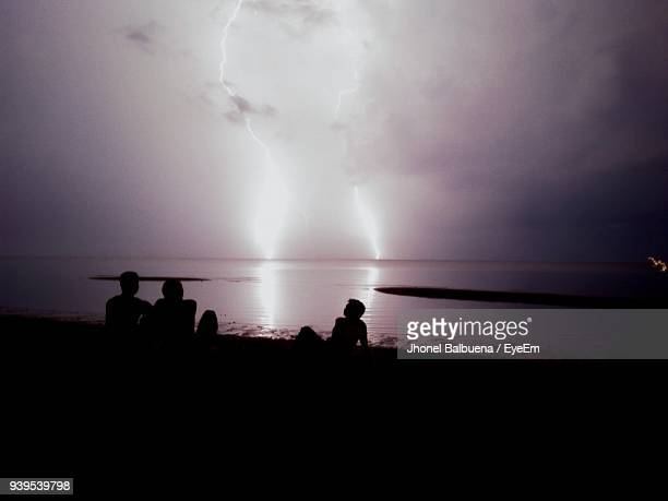 Silhouette People Sitting By Sea Against Lightning During Sunset