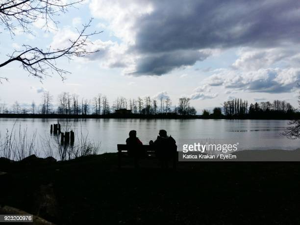 Silhouette People Sitting On Bench Against Lake During Sunset