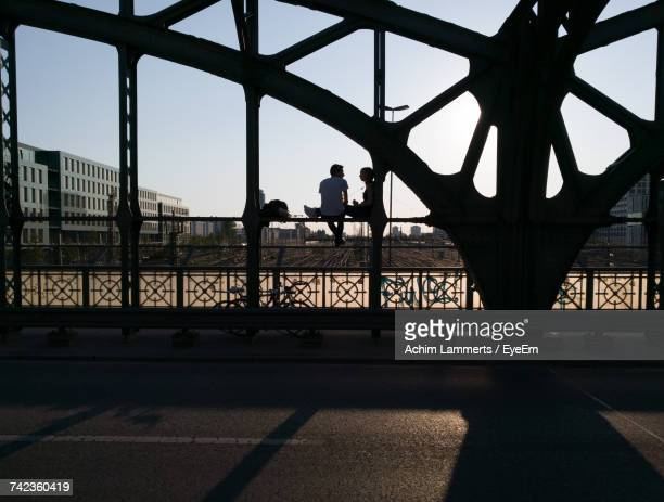 silhouette people sitting on bridge in city against sky - achim lammerts stock-fotos und bilder