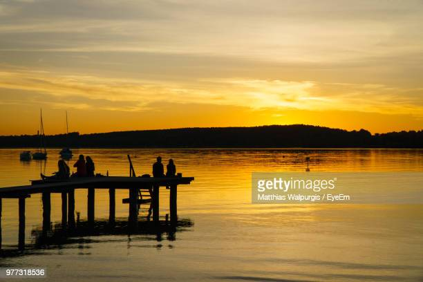 Silhouette People Sitting On Pier Over Lake Against Sky During Sunset