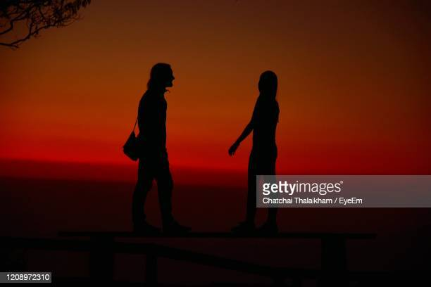 silhouette people standing against orange sky during sunset - chatchai thalaikham stock pictures, royalty-free photos & images