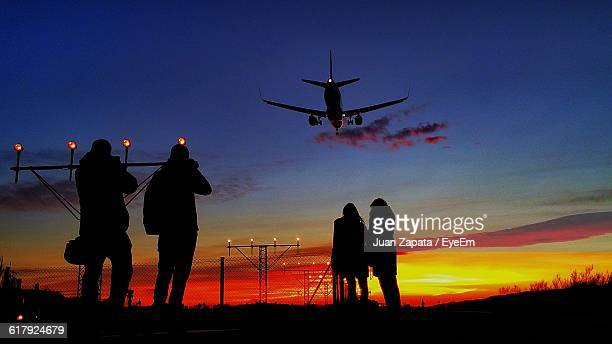 Silhouette People Standing Against Orange Sky With Airplane